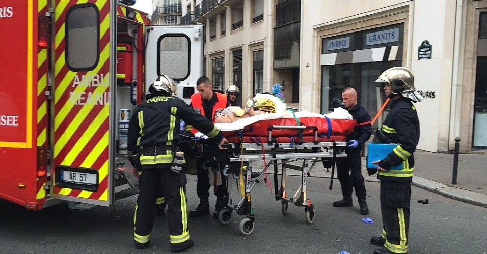 7.jan.2015 - Bombeiros resgatam um homem ferido, depois que homens armados invadiram os escritórios do jornal satírico francês Charlie Hebdo, em Paris. Pelo menos 10 pessoas morreram durante o ataque. O jornal sofreu atentados no passado após publicar charges em 2011 com piadas sobre líderes muçulmanos