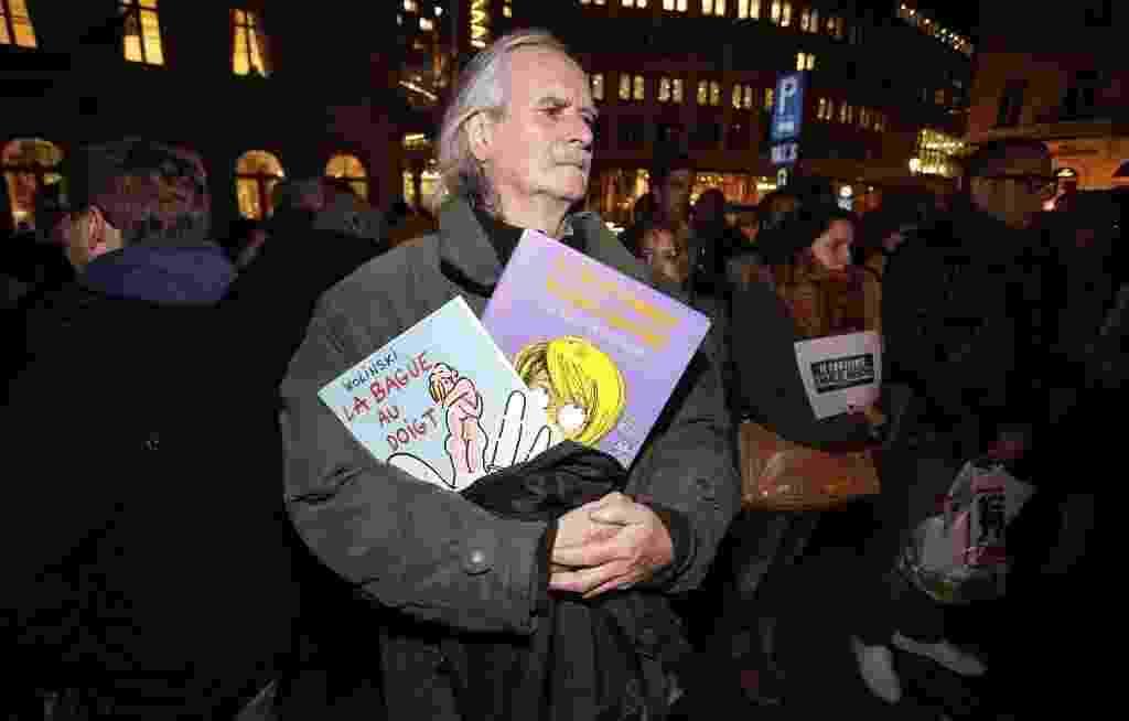 """7.jan.2015 - Dezenas de pessoas se reúnem na praça Luxemburgo, em Bruxelas, na Bélgica, para homenagear as vítimas do ataque terrorista que deixou 12 mortos na sede da revista """"Charlie Hebdo"""", em Paris nesta quarta-feira (7). Um fã do cartunista  Wolinski, um dos mortos no atentado, segura livros do ídolo durante a manifestação - Julien Warnand/ EFE"""