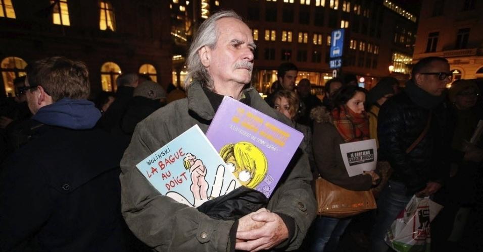 """7.jan.2015 - Dezenas de pessoas se reúnem na praça Luxemburgo, em Bruxelas, na Bélgica, para homenagear as vítimas do ataque terrorista que deixou 12 mortos na sede da revista """"Charlie Hebdo"""", em Paris nesta quarta-feira (7). Um fã do cartunista  Wolinski, um dos mortos no atentado, segura livros do ídolo durante a manifestação"""