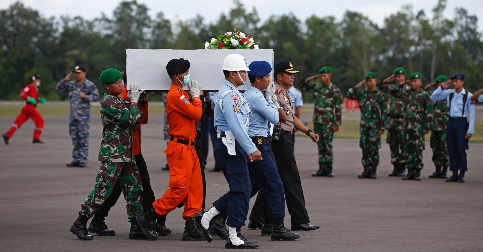 7.jan.2015 - Forças de segurança da Indonésia carregam nesta quarta-feira (7) caixão com corpo de um dos passageiros do voo da AirAsia que será encaminhado para a cidade de Surabaia, no norte da ilha de Java. O voo QZ8501 da companhia caiu no mar próximo à ilha de Borneu no último dia 28 de dezembro com 162 pessoas a bordo