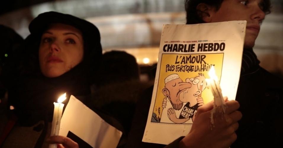 """7.jan.2015 - Jovem segura, durante ato silencioso na Place de la Republique (Praça da República), em Paris, ilustração da capa de uma edição da revista satírica francesa """"Charlie Hebdo"""". Em manifestações espontâneas convocadas em redes sociais, milhares de pessoas em cidades europeias saíram às ruas para repudiar o atentado terrorista à sede da revista """"Charlie Hebdo"""", que matou 12 pessoas, das quais oito eram jornalistas, nesta quarta-feira (7)"""