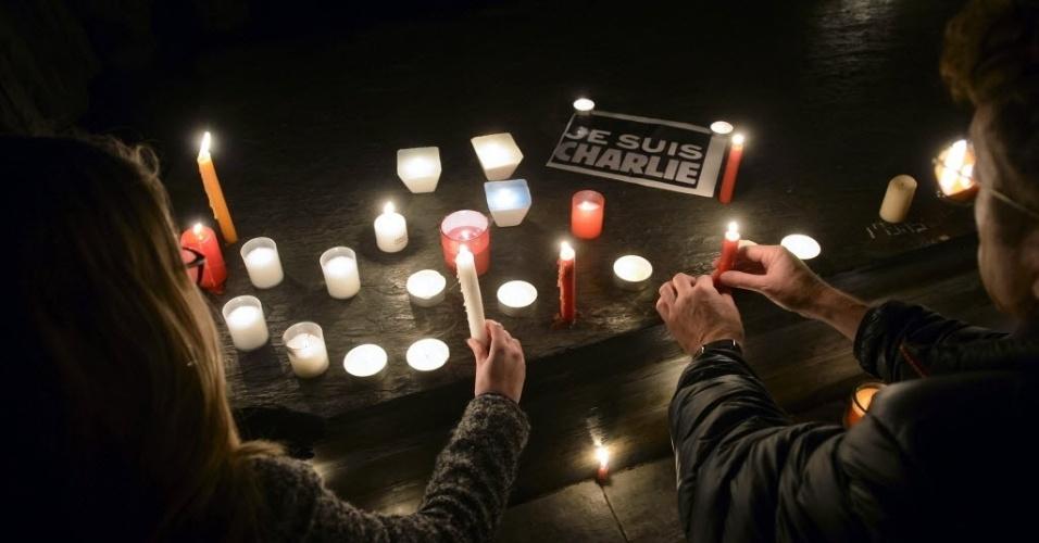 """7.jan.2015 - Velas são colocadas diante de um cartaz com a mensagem """"eu sou Charlie"""", em homenagem às vítimas do ataque feito por homens armados que invadiram o escritório da revista satírica """"Charlie Hebdo"""", na capital francesa nesta quarta-feira (7). O grupo atirou contra funcionários da publicação, matando 12 pessoas, incluindo dois policiais. Todos os serviços de segurança da França procuram pelos três homens suspeitos de terem cometido o atentado. Apenas em Paris, o contingente policial mobilizado nas buscas soma mais de 2.200 agentes"""