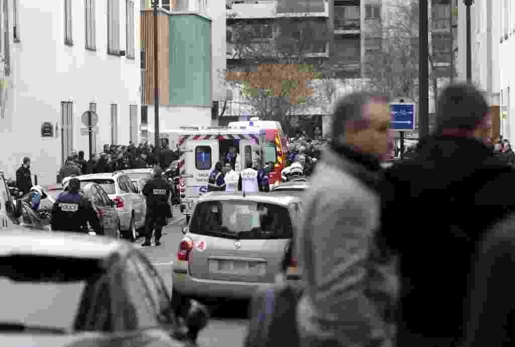 """7.jan.2015 - Bombeiros e médicos trabalham nas proximidades do escritório da revista satírica """"Charlie Hebdo"""" nesta quarta-feira (7) para ajudar as vítimas de um tiroteio iniciado por homens armados em Paris, na França. Os atiradores estavam encapuzados e usavam fuzis quando invadiram o prédio da revista francesa por volta de 11h30 no horário local (8h30 em Brasília). Na fuga, eles trocaram tiros com policiais em carros que chegavam ao local - Kenzo Tribouillard/ AFP"""