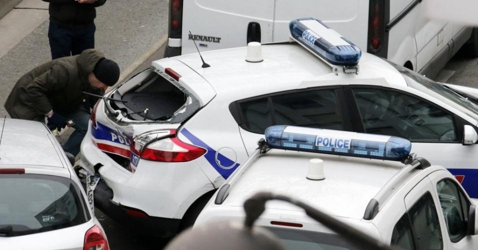 """7.jan.2015 - Policial francês analisa os danos de um carro de polícia que foi alvo de tiros durante um ataque armado à sede da revista semanal """"Charlie Hebdo"""" em Paris. Homens armados e encapuzados invadiram o escritório da publicação e abriram fogo contra funcionários, matando 12 pessoas nesta quarta-feira (7)"""