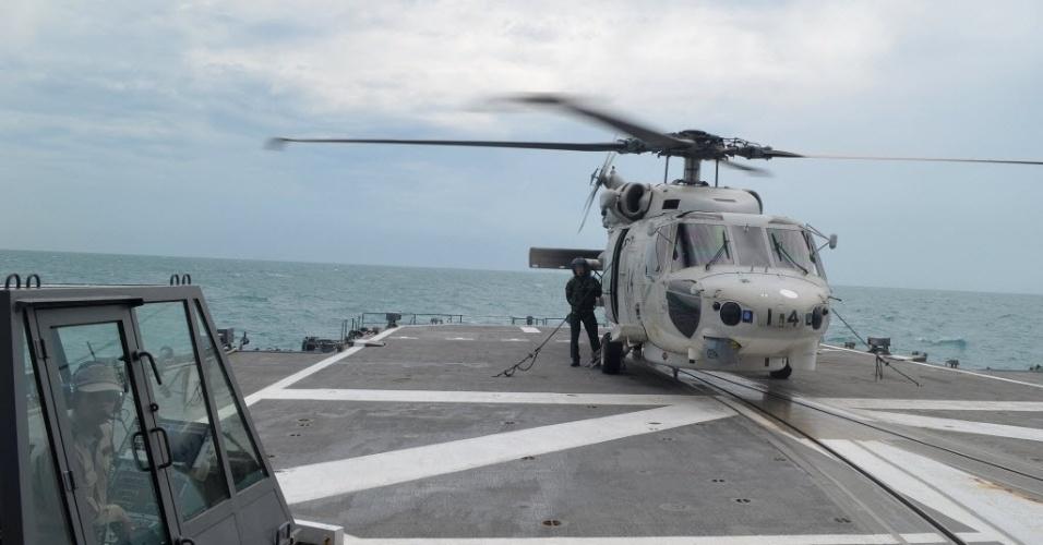 7.jan.2015 - Um helicóptero da Marinha do Japão é usado nesta quarta-feira (7) na busca por destroços do avião da AirAsia que caiu no mar de Java no último dia 28 com 162 pessoas a bordo. A cauda do avião foi encontrada e aumentou as esperanças de que as caixas-pretas sejam localizadas e revelem o que causou a queda da aeronave