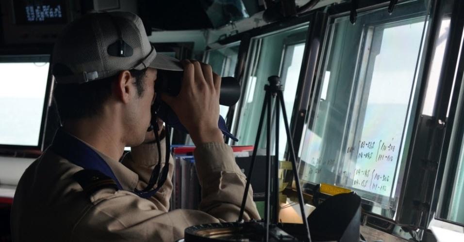 7.jan.2015 - Um membro da marinha japonesa trabalha nesta quarta-feira (7) na busca por destroços do avião da AirAsia que caiu no mar de Java no último dia 28 com 162 pessoas a bordo. A cauda do avião foi encontrada e aumentou as esperanças de que as caixas-pretas sejam localizadas e revelem o que causou a queda da aeronave