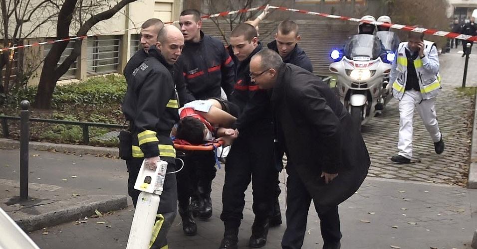 """7.jan.2015 - Um vítima do tiroteio na sede da revista francesa """"Charlie Hebdo"""" recebe ajuda de paramédicos nesta quarta-feira (7) em Paris, na França. Homens armados abriram fogo contra funcionários na sede da revista, matando ao menos 12 pessoas. O número de vítimas foi confirmado em entrevista coletiva pelo presidente François Hollande. """"Eles foram mortos covardemente. Onze pessoas estão mortas, quatro em situação de urgência absoluta. Há 40 pessoas que estão protegidas e salvas"""", declarou Hollande logo após o ataque"""