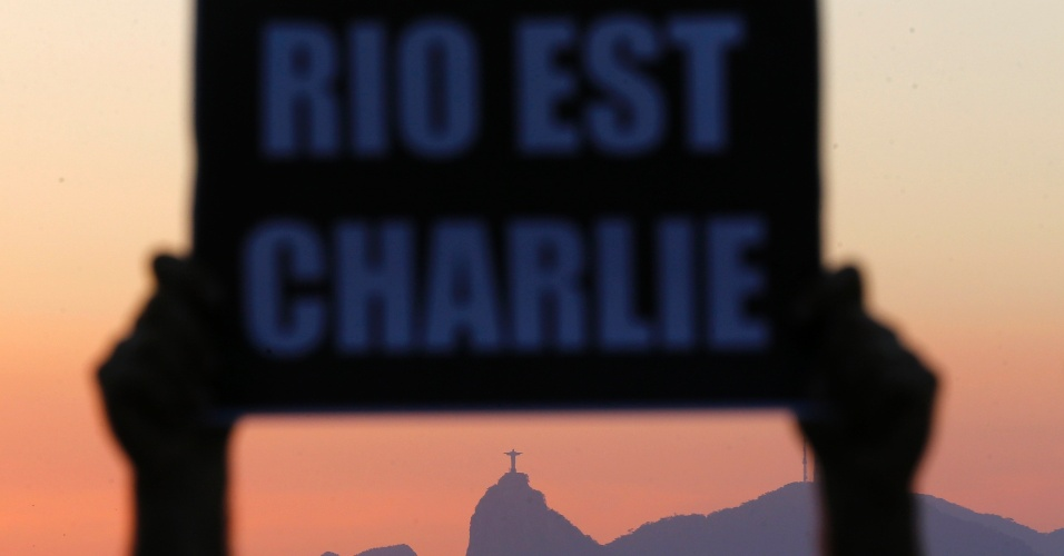 """8.jan.2014 - Um ativista da ONG Rio de Paz segura uma placa em que se lê """"Rio é Charlie"""", em homenagem às vítimas do massacre na sede da revista satírica """"Charlie Hebdo"""", em Niterói, no Rio de Janeiro. A organização convocou uma manifestação pacífica na praia, que se somou às milhares pelo mundo em tributo aos 10 jornalistas e dois policiais mortos por terroristas na quarta-feira (7) em Par"""