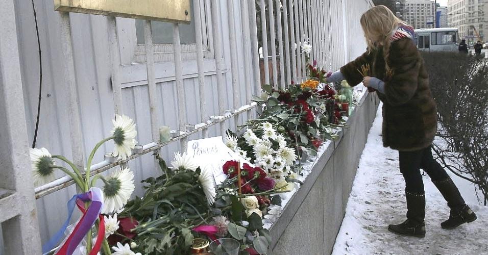 """8.jan.2014 - Uma mulher coloca flores nesta quinta-feira (8) em memória as vítimas do ataque à publicação francesa """"Charlie Hebdo"""" nos portões da Embaixada da França em Moscou, na Rússia. O primeiro-ministro da França, Manuel Valls, informou que várias pessoas foram detidas por suspeita de ter relação com o atentado contra a revista e que os dois principais suspeitos procurados estavam sendo monitorados pelas forças da ordem"""