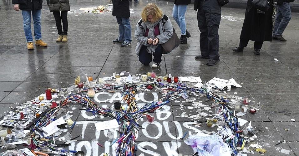 """8.jan.2014 - Uma mulher se ajoelha para acender uma vela nesta quinta-feira (8) ao lado de canetas e lápis colocados de forma que montam o símbolo da paz e do amor sobre os nomes dos cartunistas franceses mortos no ataque ao escritório da revista """"Charlie Hebdo"""" nesta quarta-feira (7) em Paris, na França. Homens armados e encapuzados invadiram a sede da revista francesa e atiraram contra funcionários em um ataque que matou ao menos 12 pessoas, segundo informações das autoridades locais. Vários suspeitos foram detidos por relação com o atentado contra a """"Charlie Hebdo"""" e os dois principais procurados já estavam sendo monitorados pelas forças da ordem"""