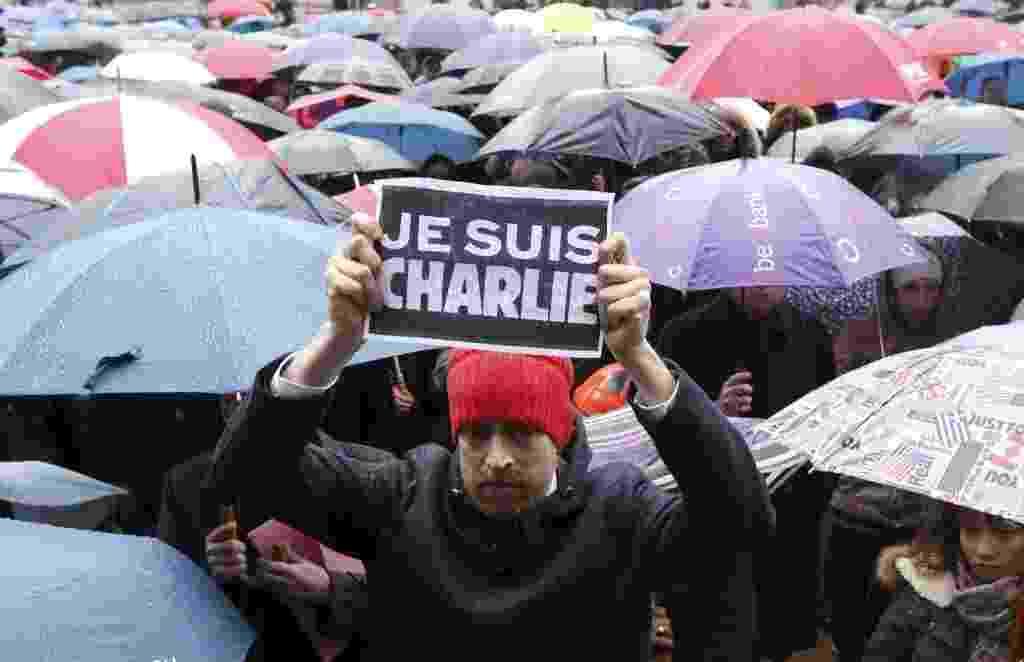 """8.jan.2015 - Belga segura um cartaz dizendo """"eu sou Charlie"""" no meio da multidão, que faz um minuto de silêncio em homenagem às vítimas do atentado contra a revista francesa """"Charlie Hebdo"""", em frente ao Parlamento da União Europeia, em Bruxelas - François Lenoir/Reuters"""