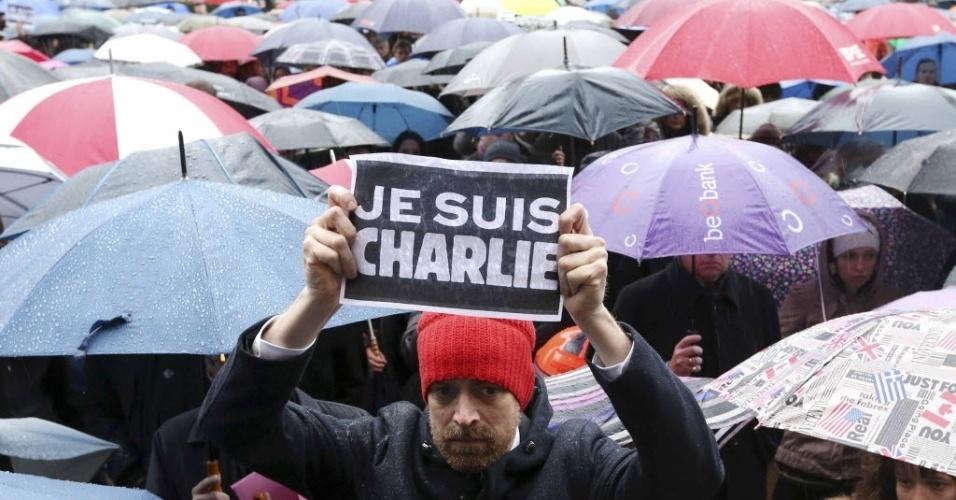 """8.jan.2015 - Belga segura um cartaz dizendo """"eu sou Charlie"""" no meio da multidão, que faz um minuto de silêncio em homenagem às vítimas do atentado contra a revista francesa """"Charlie Hebdo"""", em frente ao Parlamento da União Europeia, em Bruxelas"""