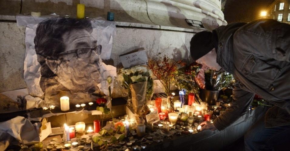 """8.jan.2015 - Francês acende uma vela ao lado de uma imagem do cartunista Bernard Verlhac, conhecido como Tignous, morto durante o ataque à revista satírica """"Charlie Hebdo"""", durante vigília na praça da República, em Paris"""