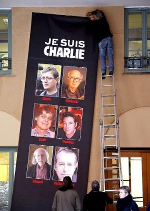 """8.jan.2015 - Francês pendura uma faixa que mostra as vítimas do atentado contra a revista """"Charlie Hebdo"""", na cidade de Nice, no sul da França. O atentado teve 12 mortos, incluindo cartunistas, funcionários e policiais"""
