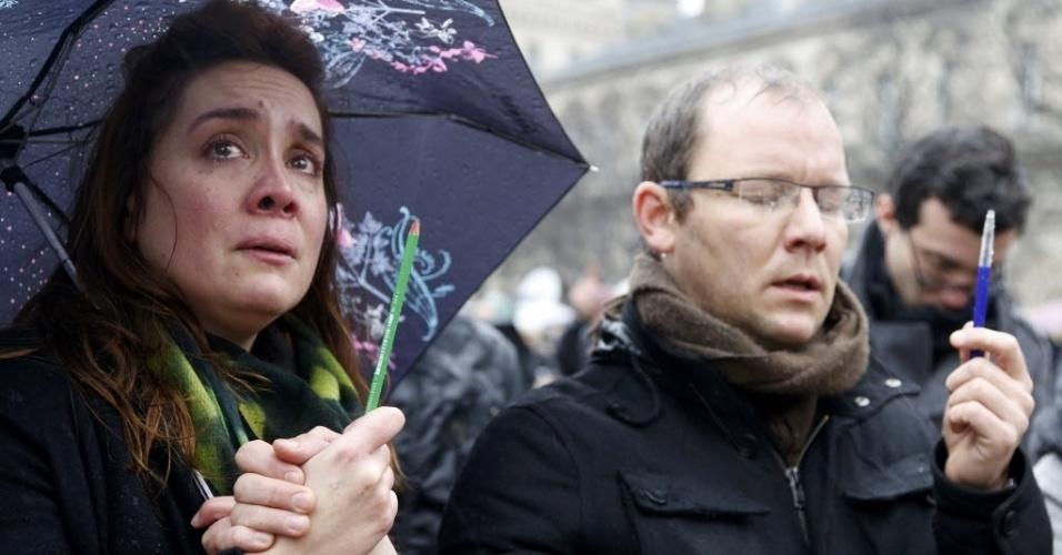 """8.jan.2015 - Francesa se emociona enquanto segura um lápis em homenagem às vítimas do ataque contra a sede da revista satírica """"Charlie Hebdo"""", em frente à Catedral de Notre Dame, em Paris"""