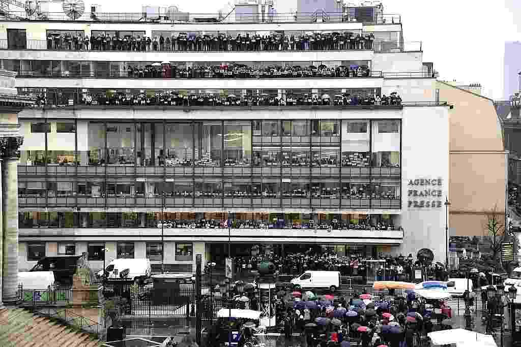"""8.jan.2015 - Jornalistas da agência de notícias AFP (Agence France-Presse) seguram cartazes dizendo """"eu sou Charlie"""" enquanto fazem um minuto de silêncio em homenagem às vítimas do atentado contra a revista """"Charlie Hebdo"""", em Paris - François Xavier Marit/AFP"""