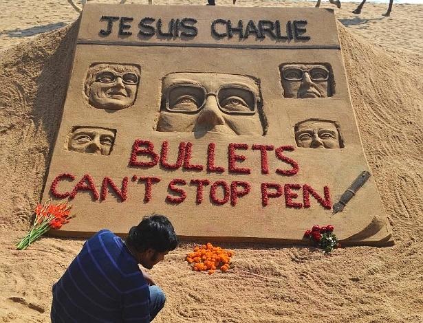 """8.jan.2015 - O artista indiano Sudarsan Pattnaik faz uma escultura de areia em homenagem às vítimas do ataque contra a sede da revista satírica francesa """"Charlie Hebdo"""", em Puri"""