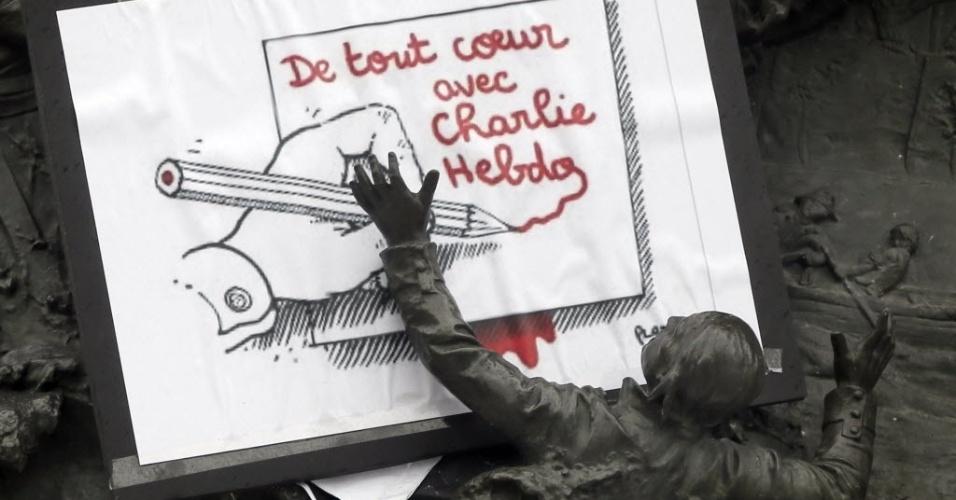"""8.jan.2015 - Uma charge feita pelo cartunista Plantu é colocado na estátua """"República"""", na praça da República, em Paris. A mensagem diz """"Plenamente com 'Charlie Hebdo'"""" (em tradução do francês)"""