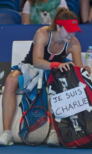"""9.jan.2015 - A tenista francesa Alizé Cornet exibe em sua bolsa o apoio à revista """"Charlie Hebdo"""" durante intervalo da partida contra a polonesa Agnieszka Radwanska válida pela Hopman Cup disputada em Perth, Austrália, nesta sexta-feira (9)"""