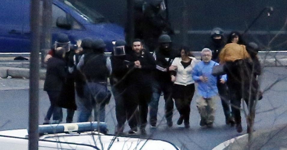 """9.jan.2015 - Equipes de segurança retiram reféns que eram ameaçados por um sequestrador em um mercado judaico no leste de Paris nesta sexta-feira (9). O suspeito foi morto depois que a polícia invadiu o local, informa o jornal francês """"Le Monde"""""""