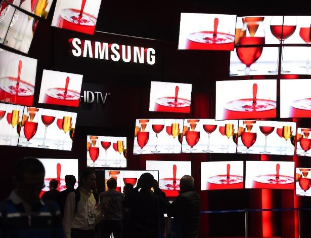 """9.jan.2015 - Estande da Samsung na CES 2015 conta com vários televisores da série SUHD 4K, da marca. Segundo a empresa sul-coreana, essa tela conta com nanocristais, o que proporciona """"maior pureza de cores e eficiência de luz"""". Além disso, a TV tem o sistema operacional Tizen, disponível pela própria companhia. Não há previsão para lançamento dos modelos SUHD no Brasil"""