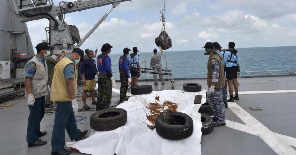 9.jan.2015 - Membros da Marinha indonésia resgatam dois corpos de vítimas do voo QZ8501 durante uma operação para recuperar a cauda da aeronave da AirAsia, no mar Java