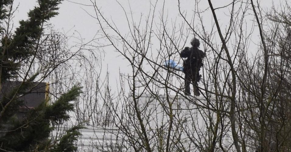 """9.jan.2015 - Policial se posiciona em uma árvore em frente a um prédio onde Chérif e Saïd Kouachi, supostos autores do massacre da quarta-feira na redação da revista """"Charlie Hebdo"""", estariam entrincheirados, na cidade de Dammartin-en Goële, a aproximadamente 40 quilômetros de Paris, na França"""