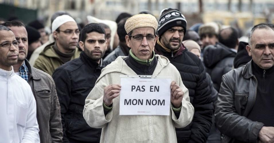 """9.jan.2015 - Um homem muçulmano segura um cartaz com os dizeres """"Não em meu nome"""" (tradução do francês) durante ato próximo à mesquita de Saint-Etienne, no leste da França, nesta sexta-feira (9), após ataque terrorista à revista satírica semanal """"Charlie Hebdo"""", que deixou 12 mortos"""