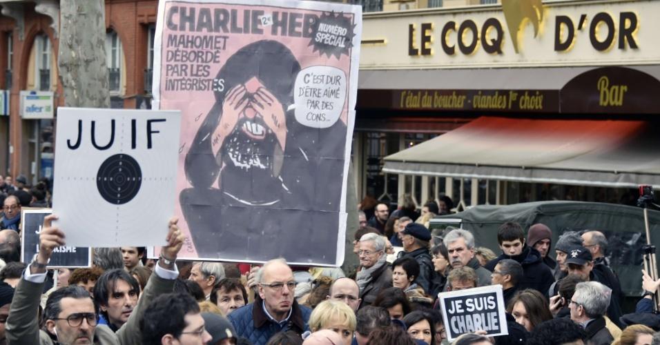 10.jan.2015 - As ruas de Toulouse reuniram cerca de 80 mil pessoas neste sábado em homenagens às vítimas dos atentados terroristas na França. Na foto, manifestante mostra placa com a palavra 'judeu' dentro de um alvo; ao lado, uma cópia de uma capa da revista 'Charlie Hebdo'