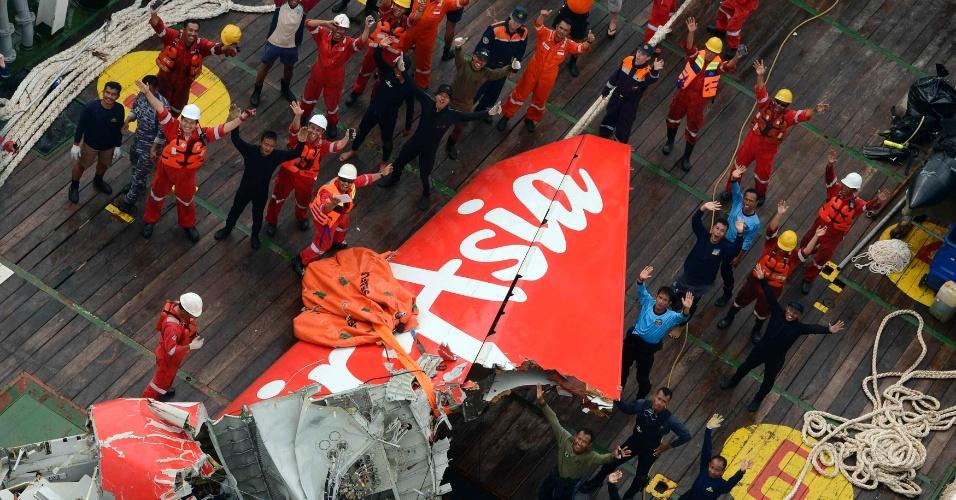 10.jan.2015 - Integrantes da equipe de buscas do avião da AirAsia que caiu em 28 de dezembro comemoram a retirada da cauda da aeronave do mar de Java, na região da Indonésia, neste sábado (10). O voo QZ 8501, que tinha como destino Cingapura, sumiu dos radares horas após a decolagem. Nenhuma das 162 pessoas a bordo - entre passageiros e tripulação - sobreviveu