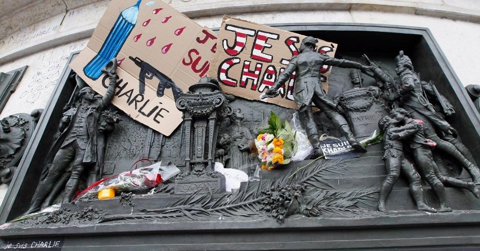 """10.jan.2015 - Um cartaz com charge do cartunista francês Plantu é visto entre outras homenagens à equipe da revista satírica """"Charlie Hebdo"""" em monumento da praça da República em Paris, neste sábado (10). Um ataque à redação na última quarta-feira (7) deixou 12 mortos, incluindo alguns dos mais famosos cartunistas da França. Houve ainda dois sequestros que terminaram com outras cinco vítimas, além da morte dos três sequestradores, incluindo os irmãos suspeitos pelo ataque à revista"""