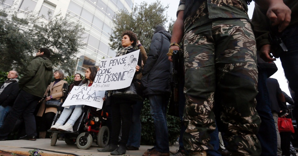 11.jan.2015 - Soldado monta guarda em Beirute, no Líbano, diante de pessoas que carregam cartazes contra o terrorismo e em solidariedade às vítimas dos atentados na França. Um dos cartazes diz ''Eu penso, logo desenho #EuSouCharlie''
