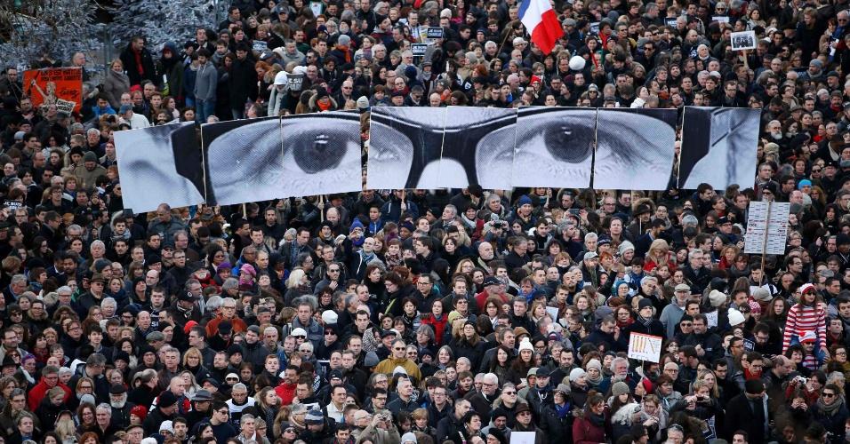 11.jan.2015 - Durante a ''Marcha Republicana'' em Paris, cidadãos parisienses seguram painel com os olhos de Charb, apelido de Stephane Charbonnier, editor da revista ''Charlie Hebdo'', morto em um atentado terrorista à publicação na última semana. Mais 16 pessoas foram vítimas de ataques