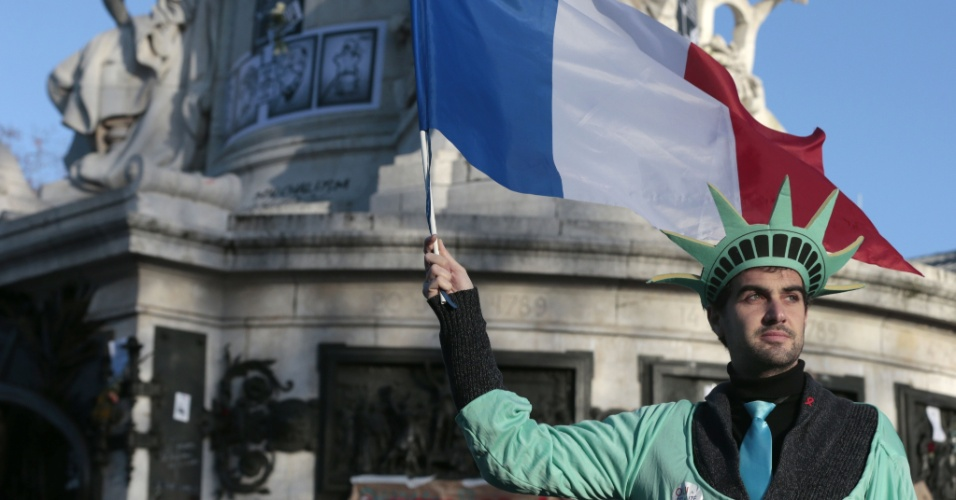 11.jan.2015 - Homem se fantasia de estátua da Liberdade e segura a bandeira francesa na Place de La Republique, em Paris, onde deve acontecer, neste domingo (11), uma marcha em memória das vítimas dos atentados terroristas na França. Cerca de um milhão de pessoas e autoridades estrangeiras são esperadas na manifestação