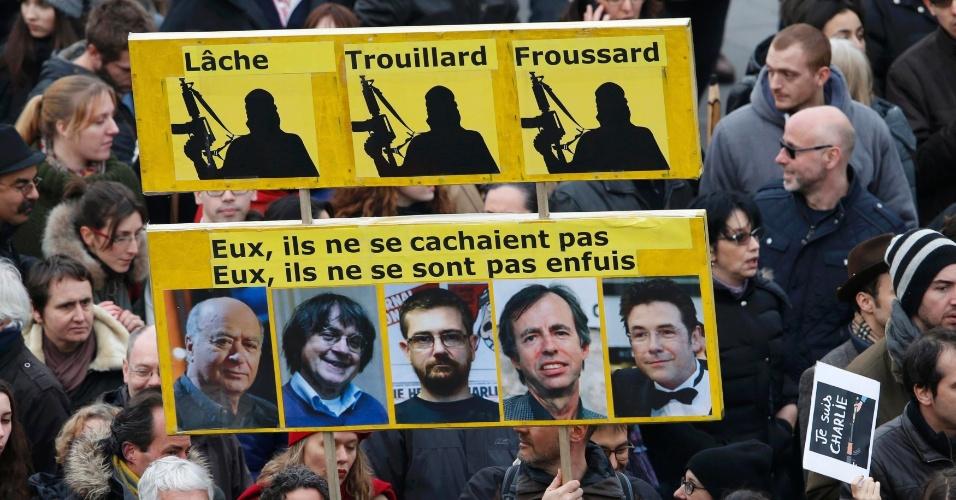 """11.jan.2015 - Manifestantes em Paris carregam um cartaz com a frase ''Medroso, Covarde e Apavorado'', no topo, e abaixo, ''Eles não se esconderam. Eles não correram'', em referência aos cartunistas e jornalistas mortos no ataque à redação da revista """"Charlie Hebdo"""" na última semana. Mais de 1 milhão de pessoas saíram às ruas da capital francesa em protesto contra o terrorismo e pela liberdade de expressão"""