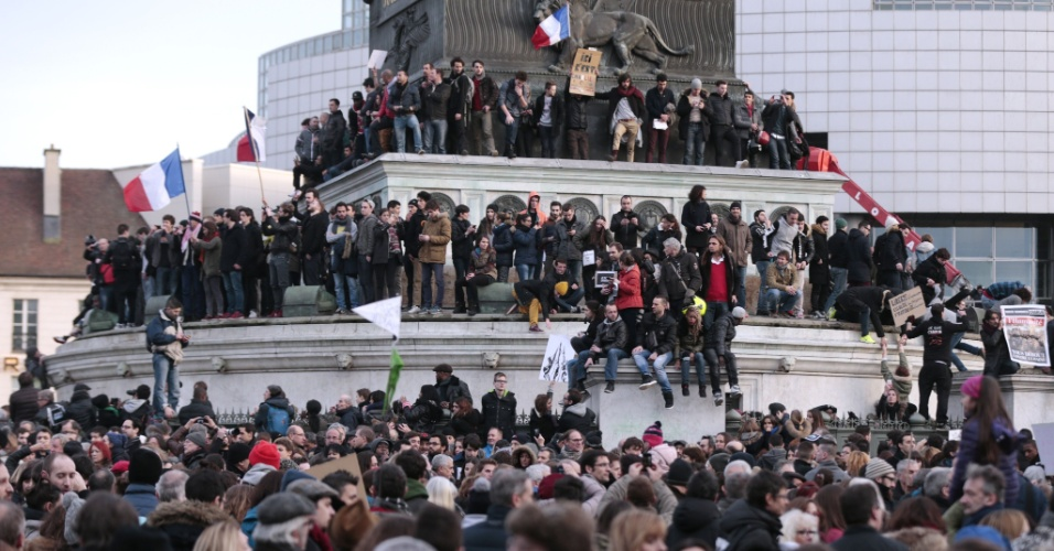 """11.jan.2015 - Manifestantes sobem em monumento na praça da Bastilha, em Paris, neste domingo, durante a """"Marcha Republicana"""" contra os atentados terroristas na França. Estima-se que mais de 1 milhão de pessoas estejam participando do protesto na capital francesa"""