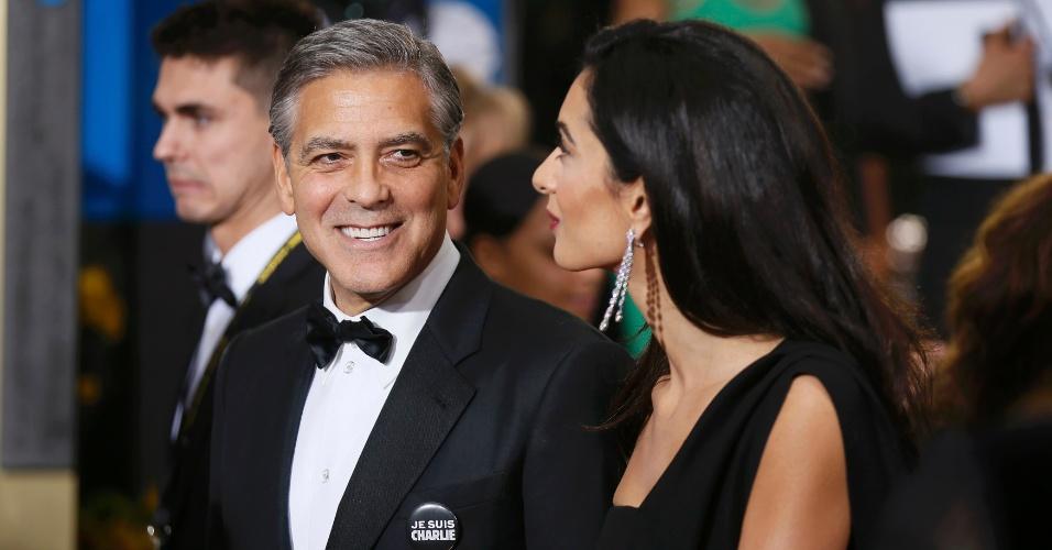 """11.jan.2015 - O ator americano George Clooney e sua mulher, a advogada Amal, chegam neste domingo (11) para o Globo de Ouro, em Beverly Hills, na California. Clooney usava um acessório com a frase """"eu sou Charlie"""", que se tornou lema de resistência após o ataque à revista satírica """"Charlie Hebdo"""", na França. Neste domingo, manifestantes em várias cidades do mundo todo fizeram homenagem aos 17 mortos nos atentados e deram apoio à """"Marcha Republicana"""", que movimentou 4 milhões na França"""