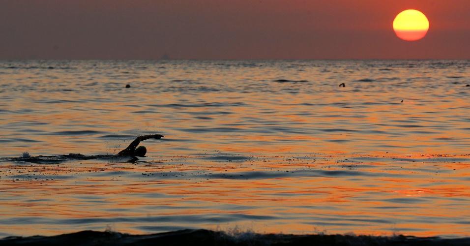 12.jan.2015 - Banhista nada nas águas da praia de Copacabana, logo após o nascer do sol nesta segunda-feira (12) no Rio de Janeiro