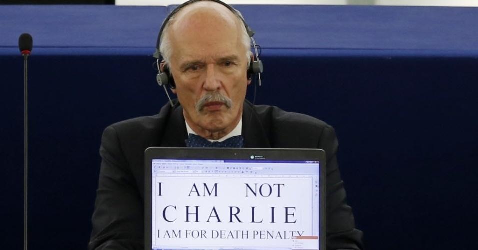 """112.jan.2015 - Membro do Parlamento Europeu, Janusz Korwin-Mikke, exibe o cartaz """"Não sou Charlie, sou a favor da pena de morte"""" na tela de seu computador, em Estrasburgo, na França, nesta segunda-feira (12), durante um debate sobre os atentados terroristas da semana passada. Os ataques começaram no dia 7 de janeiro com a invasão do escritório da revista satírica """"Charlie Hebdo"""", em Paris, que terminou com 12 mortos. Outras cinco pessoas foram vítimas de ataques terroristas"""