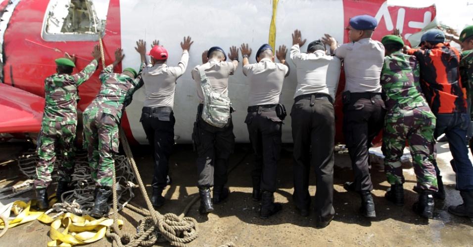 12.jan.2015 - Soldados indonésios movem a cauda do avião AirAsia QZ8501 durante operação de resgate dos destroços retirados do mar de Java nesta segunda-feira (12). As equipes retiraram do mar uma das caixas-pretas da aeronave, que caiu há duas semanas com 162 pessoas a bordo