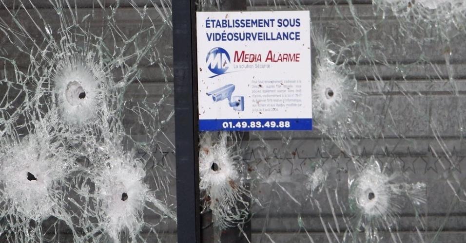12.jan.2015 - Buracos feitos por tiros podia ser vistos nesta segunda-feira (12) nas portas do supermercado judaico Hyper Casher em Paris, na França, onde quatro reféns foram mortos na última sexta-feira (9) durante sequestro organizado por um extremista islâmico. Escolas judaicas e sinagogas na França pediram proteção extra, até do Exército, após os assassinatos cometidos por militantes islâmicos na semana passada