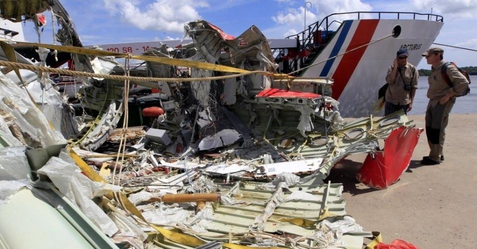 """12.jan.2015 - Dois pesquisadores analisam os destroços recuperados do avião da AirAsia que caiu há duas semanas no mar de Java, com 162 pessoas a bordo. De acordo com uma fonte próxima às investigações, dados do radar da aeronave aparentemente mostram que o avião fez uma subida brusca para evitar as tempestades que assolavam a região e ficou num ângulo """"inacreditavelmente"""" inclinado antes da queda"""