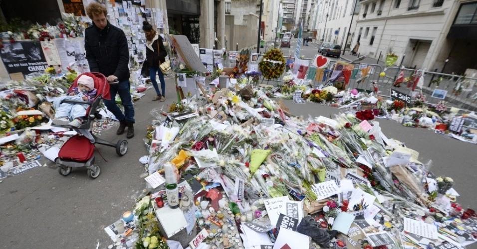 """12.jan.2015 - Franceses enfeitam com flores o memorial improvisado em frente ao escritório da revista """"Charlie Hebdo"""" nesta segunda-feira (12) em Paris, na França, em homenagem às 17 vítimas dos ataques terroristas. Após os atentados, mais de 50 atos antimuçulmanos foram registrados pela França, de acordo com o Observatório contra a Islamofobia do Conselho Francês de Culto Muçulmano (CFCM), que pediu ao Estado que reforce a vigilância das mesquitas. Segundo o presidente deste órgão, Abdullah Zekri, desde quarta-feira (7) passada foram contabilizadas 21 ações (disparos, lançamentos de granadas, etc.) e 33 ameaças (cartas, insultos, etc.)"""