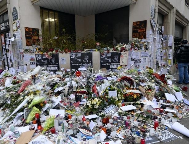 """12.jan.2015 - Franceses enfeitam com flores o memorial improvisado em frente ao escritório da revista """"Charlie Hebdo"""" nesta segunda-feira (12) em Paris, na França, em homenagem às 17 vítimas dos ataques terroristas. Desde o atentado jihadista à sede da revista satírica no dia 7 de janeiro, mais de 50 atos antimuçulmanos foram registrados pela França, de acordo com o Observatório contra a Islamofobia do Conselho Francês de Culto Muçulmano (CFCM), que pediu ao Estado que reforce a vigilância das mesquitas. Segundo o presidente deste órgão, Abdullah Zekri, nesse período foram contabilizadas 21 ações (disparos, lançamentos de granadas, etc.) e 33 ameaças (cartas, insultos, etc.)"""