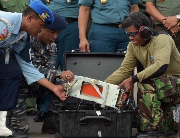 12.jan.2015 - Oficiais indonésios transportam uma das caixas-pretas recuperada do avião da AirAsia que caiu há duas semanas no mar de Java, com 162 pessoas a bordo. As caixas-pretas foram detectadas no domingo (11) a uma profundidade entre 30 e 32 metros, mas não puderam ser recuperadas antes por estarem presas entre os destroços do aparelho