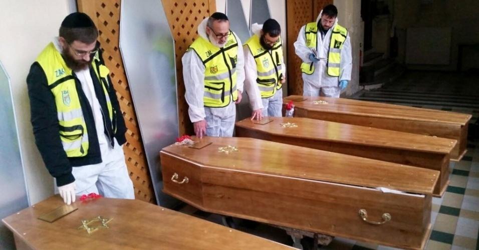12.jan.2015 - Quatro homens oram nesta segunda-feira (12) ao lado dos caixões das quatro vítimas judias que morreram durante o sequestro em um supermercado em Paris, na França, antes dos corpos serem repatriados para Israel. A capital francesa viveu três dias de terror na semana passada com ataques jihadistas que mataram 17 pessoas. Após os atentados, mais de 50 atos antimuçulmanos foram registrados pela França, de acordo com o Observatório contra a Islamofobia do Conselho Francês de Culto Muçulmano (CFCM), que pediu ao Estado que reforce a vigilância
