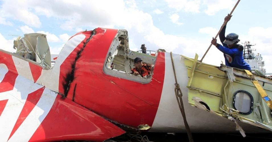 12.jan.2015 - Trabalhadores indonésios inspecionam os destroços do avião da AirAsia que caiu há duas semanas no mar de Java, com 162 pessoas a bordo. O voo QZ8501 decolou da cidade de Surabaia às 5h20 locais do dia 28 de dezembro e deveria chegar a Cingapura duas horas depois, mas caiu no mar de Java após 40 minutos da decolagem. A caixa-preta que contém o registro de voo foi encontrada e poderá esclarecer o que causou a queda da aeronave