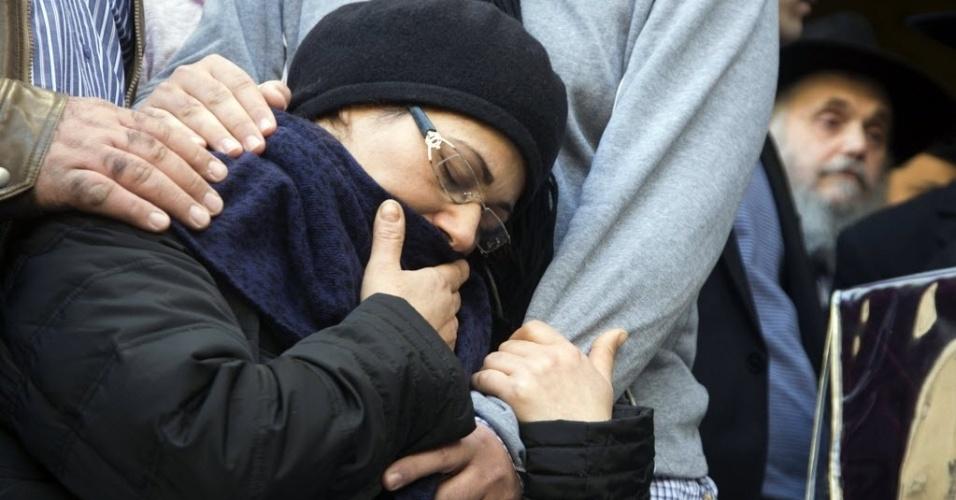 13.jan.2015 - A mãe do judeu francês Yoav Hattab, umas das vítimas do ataque a um mercado kosher de Paris, se emociona próximo ao caixão antes da procissão funerária nesta terça-feira (13), em Israel