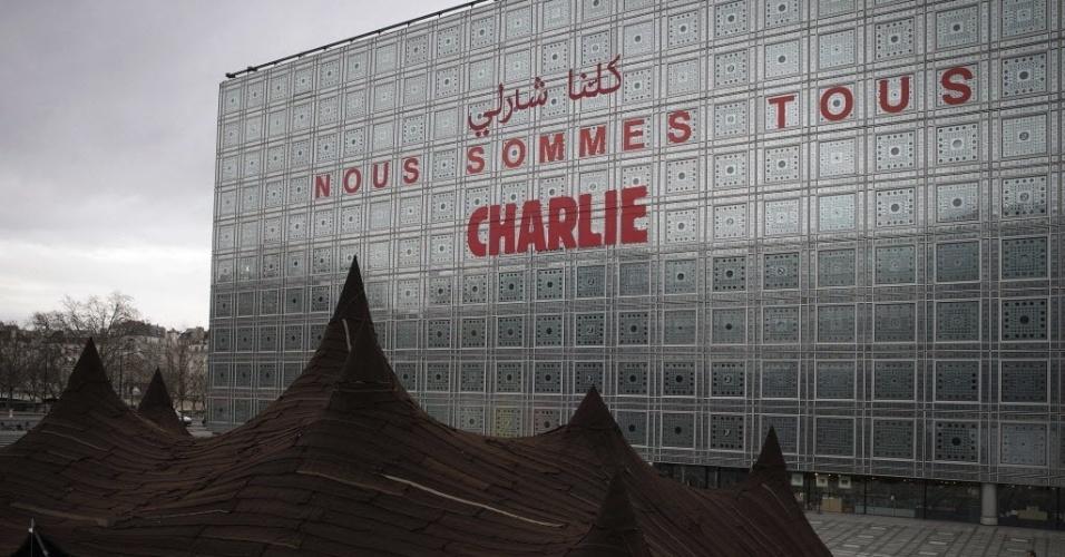"""13.jan.2015 - A frase """"Nous sommes tous Charlie"""" (Nós todos somos Charlie) em árabe e francês foi colocada na fachada do Instituto do Mundo Árabe, em Paris, na França, em homenagem às 17 vítimas de atentados terroristas que ocorreram no país"""