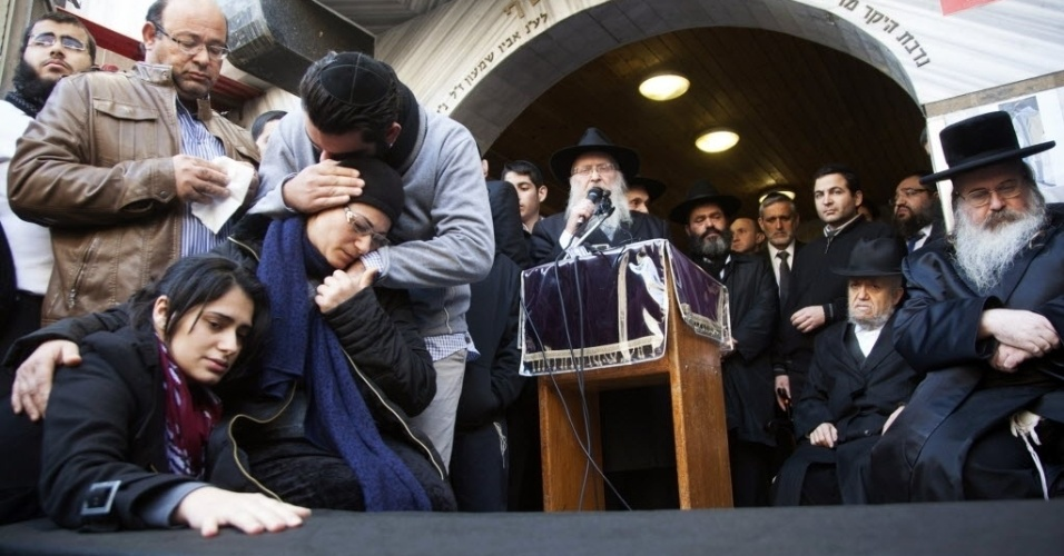 13.jan.2015 - A mãe e a irmã de Yoav Hattab, umas das vítimas do ataque a um mercado kosher de Paris, choram ao lado caixão antes do cortejo funerário nesta terça-feira (13), em Israel